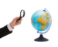 Businessman hand holding magnifier over globe travel earth geography and business concept close up of magnifying glass earth Stock Images