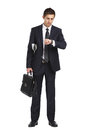 Businessman handing briefcase and looking at his watch full length portrait of isolated on white concept of business success Stock Photos