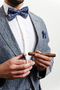 Businessman with handkerchief in a suit blue and bow tie cutting cigare Stock Photos