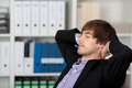 Businessman with hands behind head and closed eyes relaxed young in office Royalty Free Stock Photo