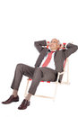 Businessman with hands behind head relaxing on deck chair full length of mature against white background Stock Photo