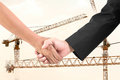 Businessman handshake in construction crane partners shaking hands with Royalty Free Stock Photos