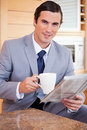 Businessman having coffee and reading news in the kitchen Stock Images
