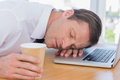 Businessman having a nap on his laptop while he is holding cup of coffee Stock Images