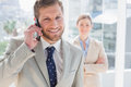 Businessman having phone conversation and smiling at camera with colleague standing behind him Stock Photo