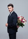 Businessman hiding bouquet of flowers behind his back over gray background and looking at camera Stock Photo