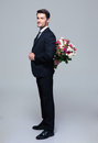 Businessman hiding bouquet of flowers behind his back over gray background and looking at camera Royalty Free Stock Images