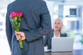 Businessman hiding flowers behind back for colleague in office Stock Images