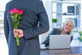 Businessman hiding flowers behind back for colleague in office Stock Photo