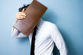 Businessman hiding his face behind an old briefcase on blue background Stock Photos