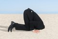 Businessman hiding his head in sand side view of Stock Photos