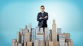 A businessman with his hands crossed standing behind a small model of a business district. Royalty Free Stock Photo