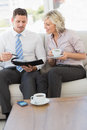 Businessman and his secretary with diary and tea cup smart on sofa at home Royalty Free Stock Photo