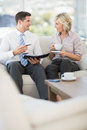 Businessman and his secretary with diary and tea cup smart on sofa at home Stock Photography