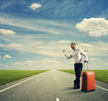 Businessman hitch hiking on a road smiley young Royalty Free Stock Photography
