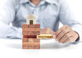 Businessman hold word investment on puzzle with wooden home model Royalty Free Stock Photo