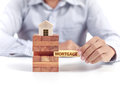 Businessman hold word mortgage on puzzle with wooden home model Royalty Free Stock Photo