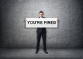 Businessman holding banner with 'you're fired' text on it in his hands Royalty Free Stock Photo