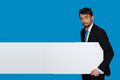 Businessman holding blank poster on blue Stock Photos