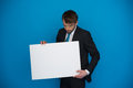Businessman holding blank poster on blue Royalty Free Stock Photo