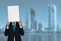 Businessman holding blank poster in a city background Royalty Free Stock Image