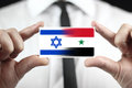 Businessman holding a business card with israel and syria flag Stock Images