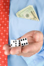 Businessman holding dice a with a pocket full of cash holds a pair of while gambling image is good for most business inferences Royalty Free Stock Photos