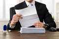 Businessman Holding Document At Desk Royalty Free Stock Photo