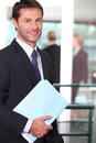 Businessman holding a file with colleagues out of focus in the background Stock Photo