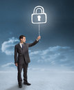 Businessman holding a floating padlock with clouds on the background Royalty Free Stock Photo