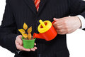 Businessman holding a flower pot and watering can Royalty Free Stock Photo