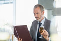 Businessman holding glass of beer and looking at menu Royalty Free Stock Photo
