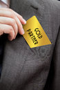 Businessman holding a gold card pulling out of his pocket Royalty Free Stock Image