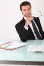 Businessman holding his glasses