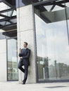 Businessman holding mobile phone while leaning on office wall full length of Royalty Free Stock Photography