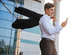 Businessman holding mobile phone walking with jacket over shoulder outdoors Royalty Free Stock Photo