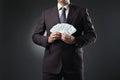 Businessman holding money in hands on dark