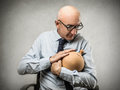 Businessman holding a moneybox and cuddling Royalty Free Stock Image