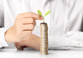 Businessman holding plant sprouting from a handful of coins Royalty Free Stock Photography