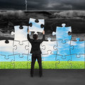Businessman holding puzzles to assembly turning bad situation change from tsunami beautiful landscape Stock Images