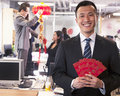 Businessman holding red envelopes and coworkers hanging decorations for chinese new year Stock Image