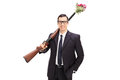 Businessman holding a rifle loaded with flowers isolated on white background Stock Photos