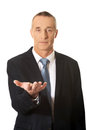 Businessman holding something on his palm smiling Royalty Free Stock Photo