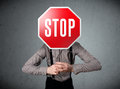 Businessman holding a stop sign standing and in front of his head Stock Photo