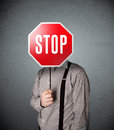Businessman holding a stop sign standing and in front of his head Royalty Free Stock Image