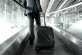 Businessman holding trolley bag going up on airport escalator Royalty Free Stock Photo