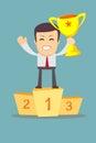 Businessman holding winner`s cup.