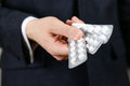 Businessman holds in hands a lot of white pills and packs of tab