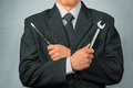 Businessman holds tools concept of business creation in a suit metal wrench and screwdriver Stock Photography