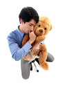 Businessman hugging teddy bear and sucking thumb Royalty Free Stock Photo